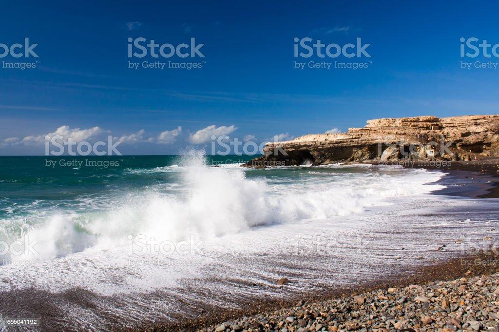 Waves crashing on the sand with sea foam stock photo