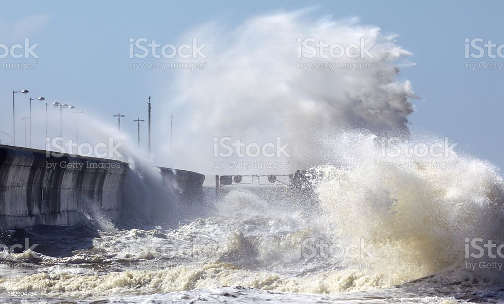 Waves crashing onto seafront in stormy weather stock photo
