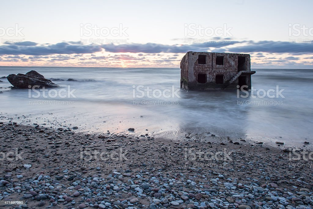 waves crushing over rocks in sunset stock photo