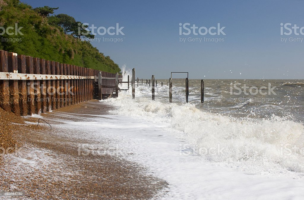 Waves hit sea defences at high water, Bawdsey, Suffolk stock photo