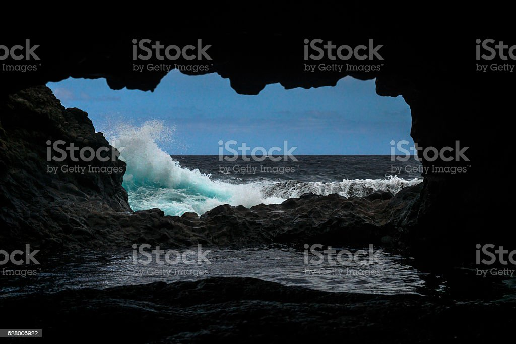 Waves in front of the coast cave stock photo