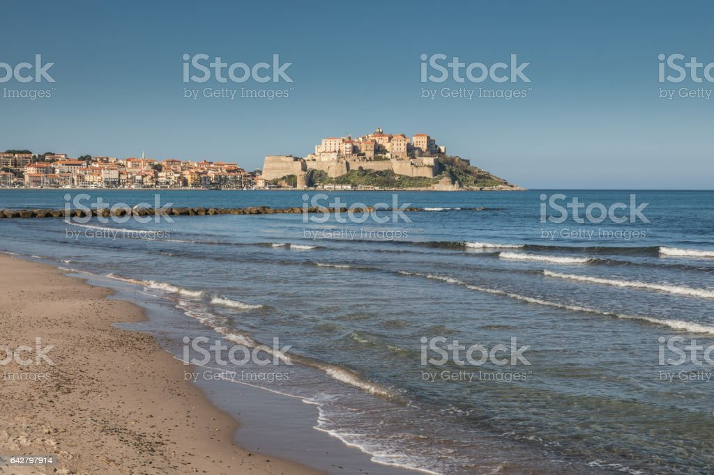 Waves lapping onto Calvi beach with Citadel and town behind stock photo
