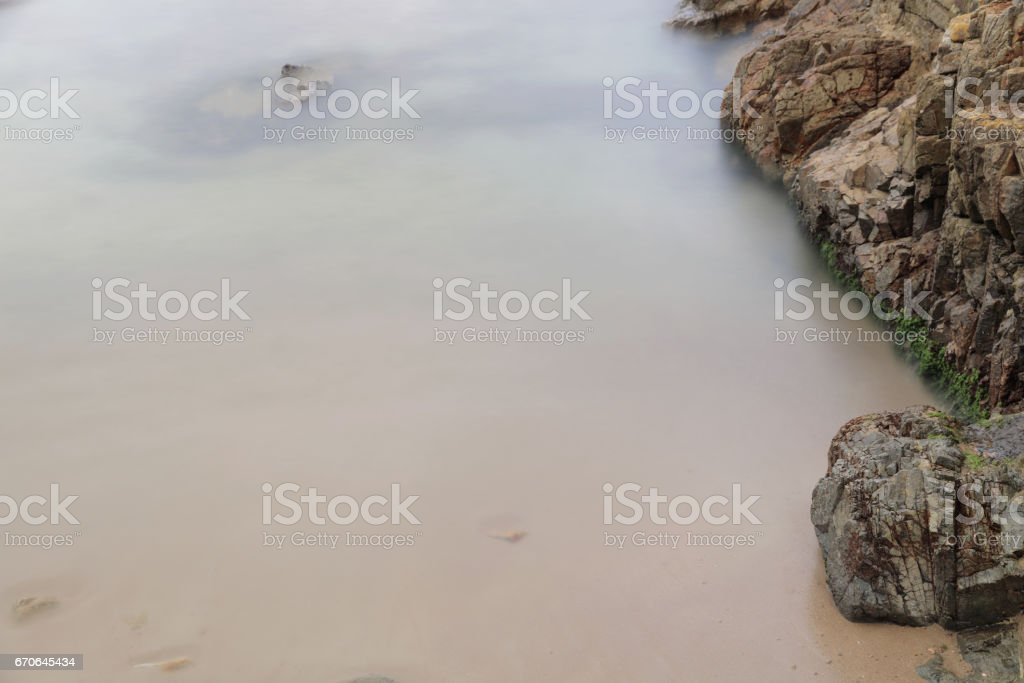 waves lash line impact rock on the beach stock photo