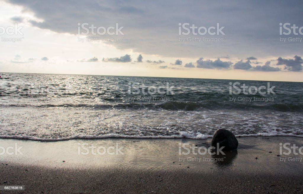 Waves of sea during sunset at cloudy sky stock photo