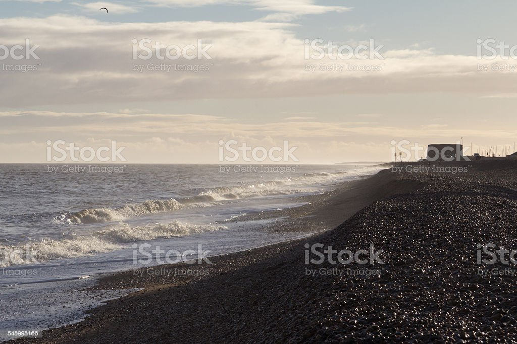 Waves on Aldeburgh beach with martello tower in background stock photo