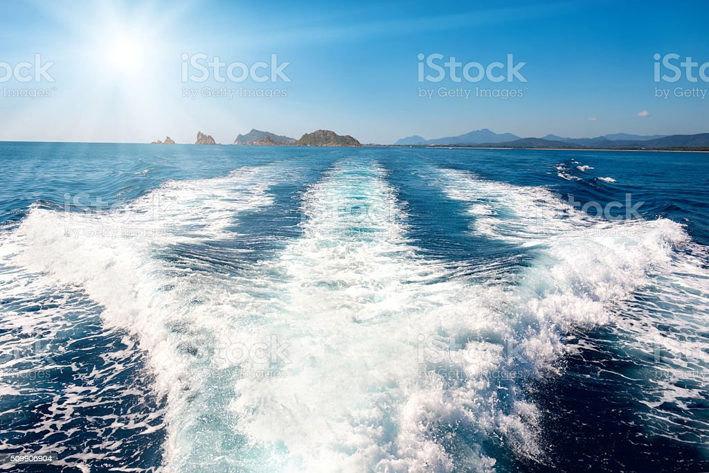Waves on blue sea behind the boat stock photo