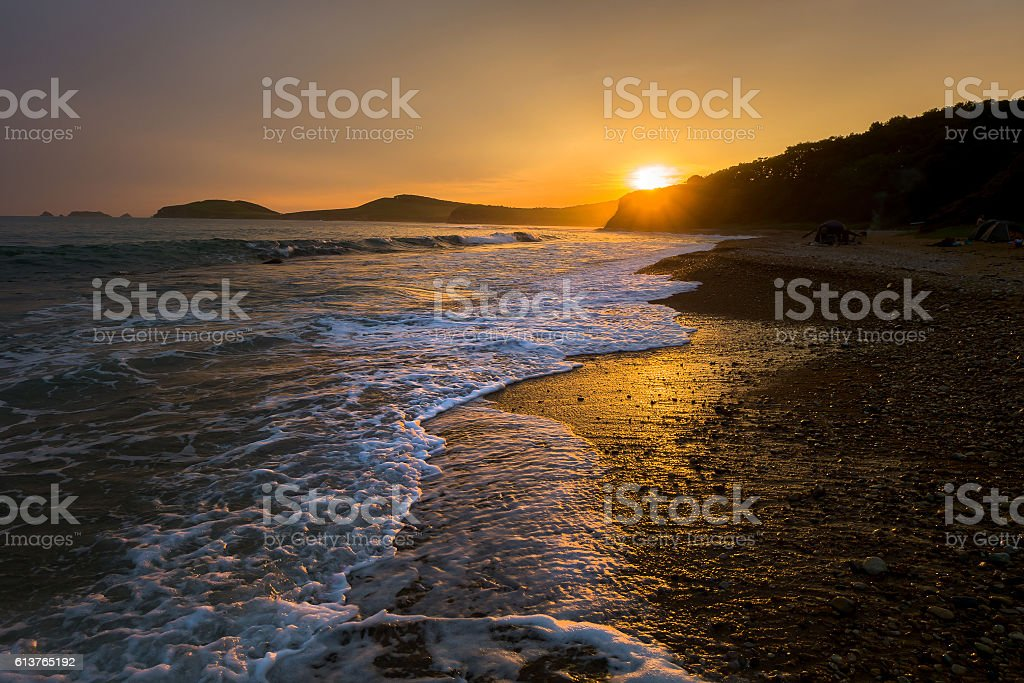 waves on the beach against sunset of russian isle Putyatin stock photo