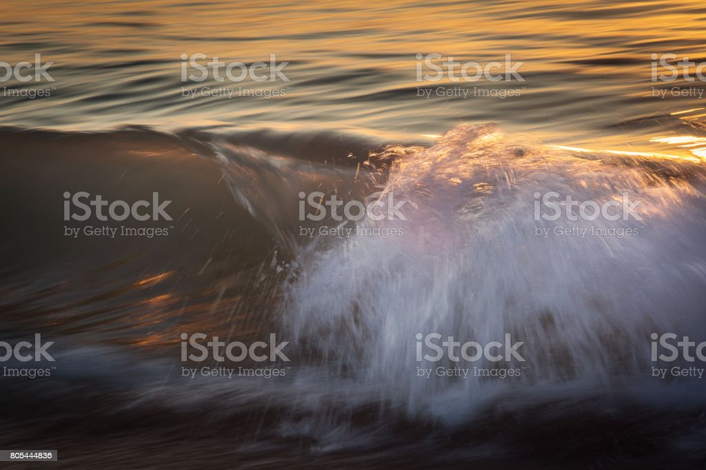 Waves on the ocean captured with a slow shutter speed to bring a sense of movement and power. stock photo