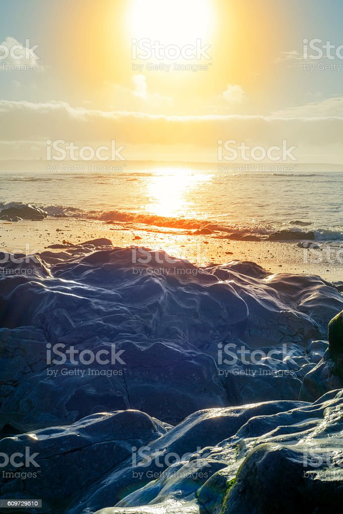 waves over hot sunset rocks stock photo