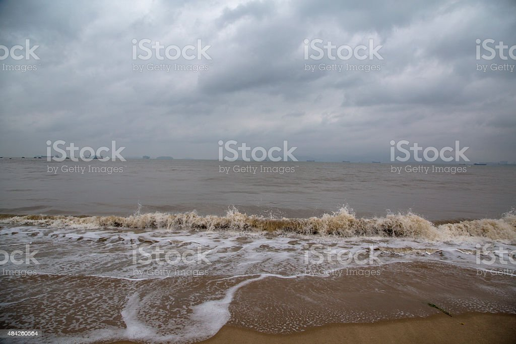 waves patting on beach on an overcast day stock photo