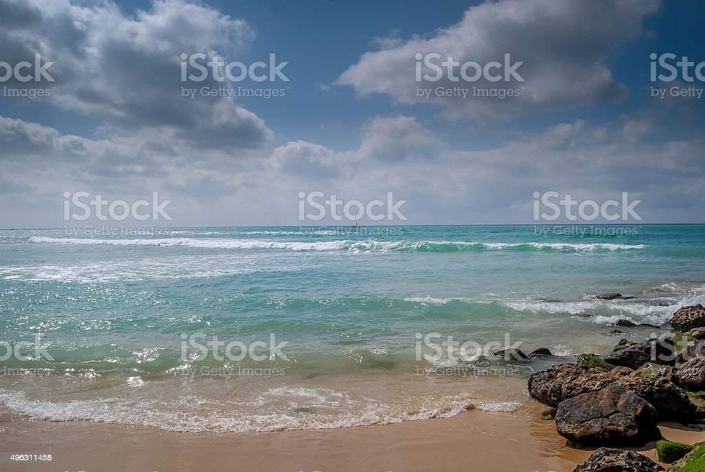 Waves, rocks and clouds stock photo