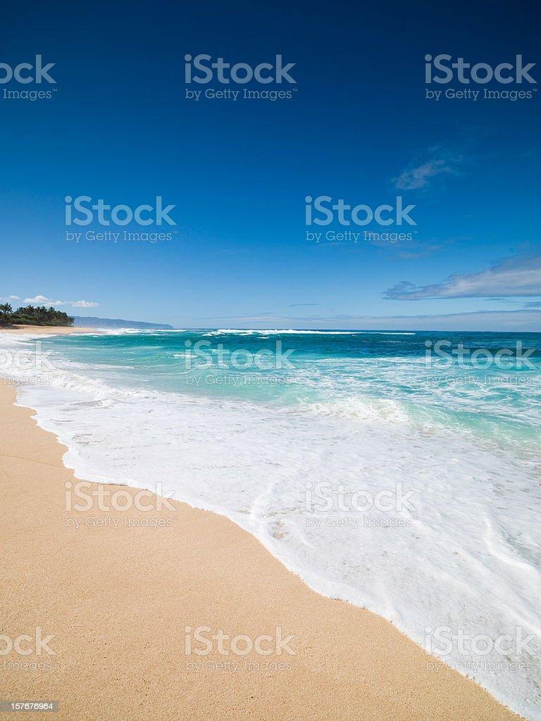 Waves splashing on a beach in Oahu, Hawaii stock photo