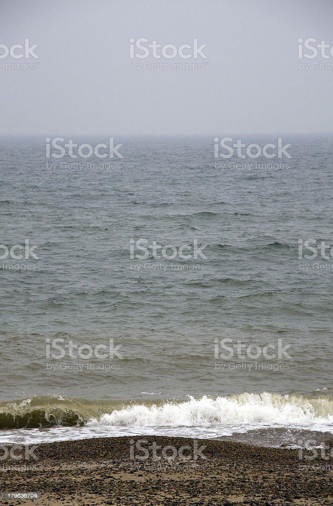 Waves splashing onto stone covered beach. royalty-free stock photo