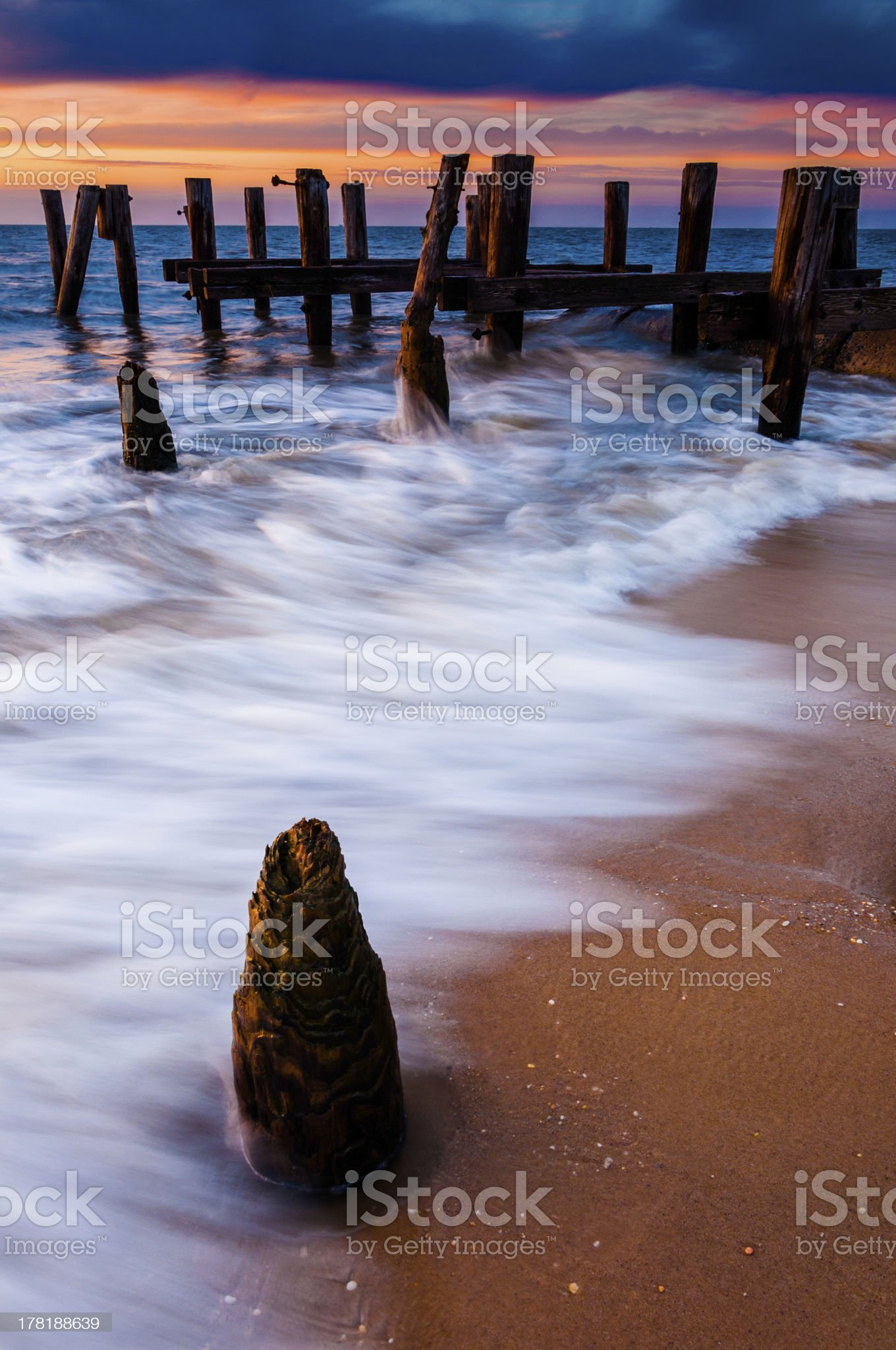 Waves swirl around pier pilings at sunset, Cape May, NJ. royalty-free stock photo