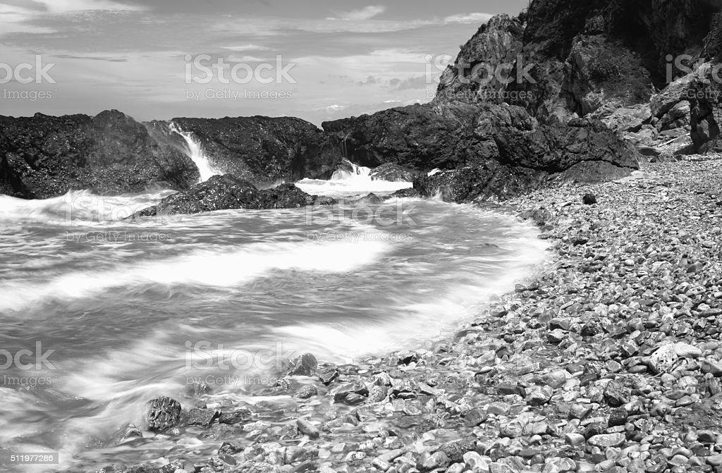 Waves wash ashore during a beautiful rock, Monochrome stock photo