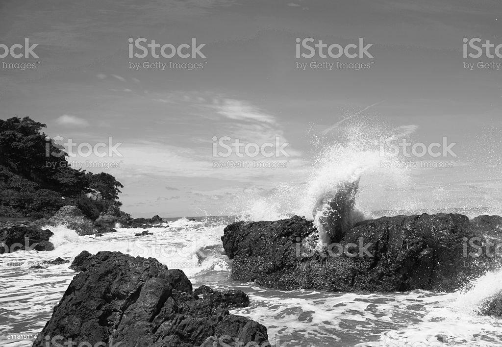Waves wash ashore during a beautiful rock stock photo