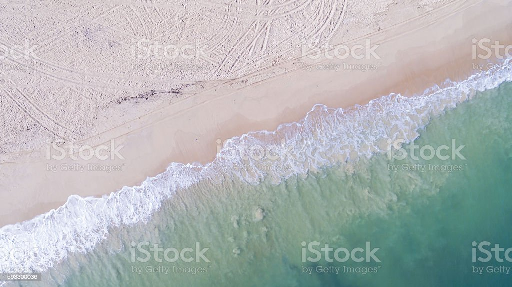 Waves Washing onto the Beach Viewed From Above stock photo