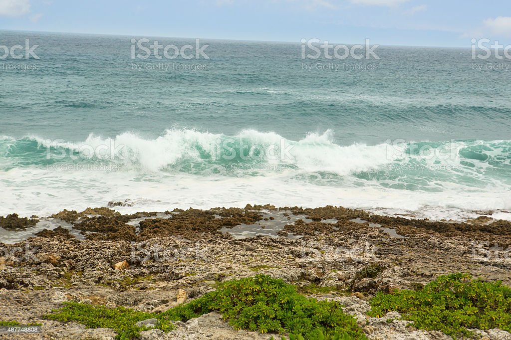 Waves washing up on rocky coral shore in Cayman Islands stock photo