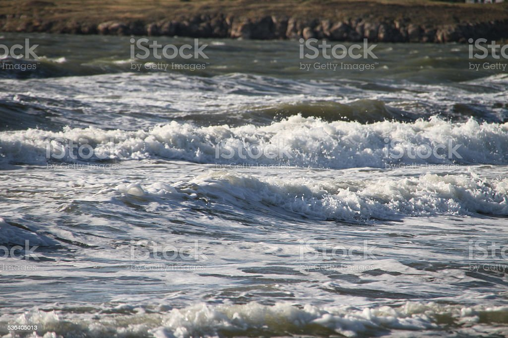 Waves with white foam storm on a clear day stock photo