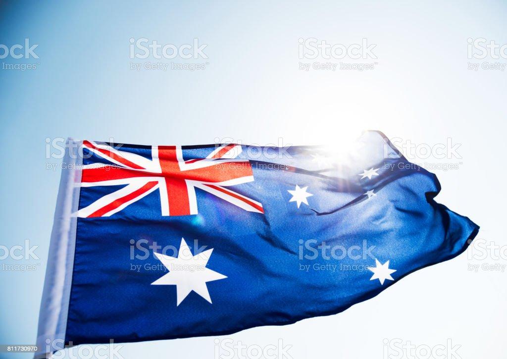 Waving Australia flag against blue sky stock photo