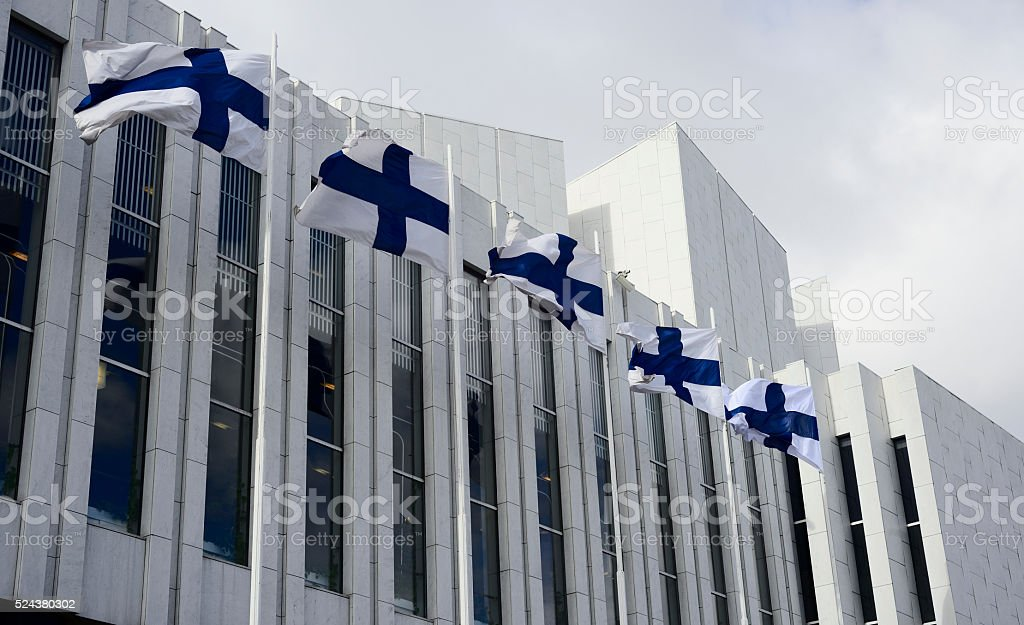 waving Finnish flags against of The Finlandia Hall stock photo