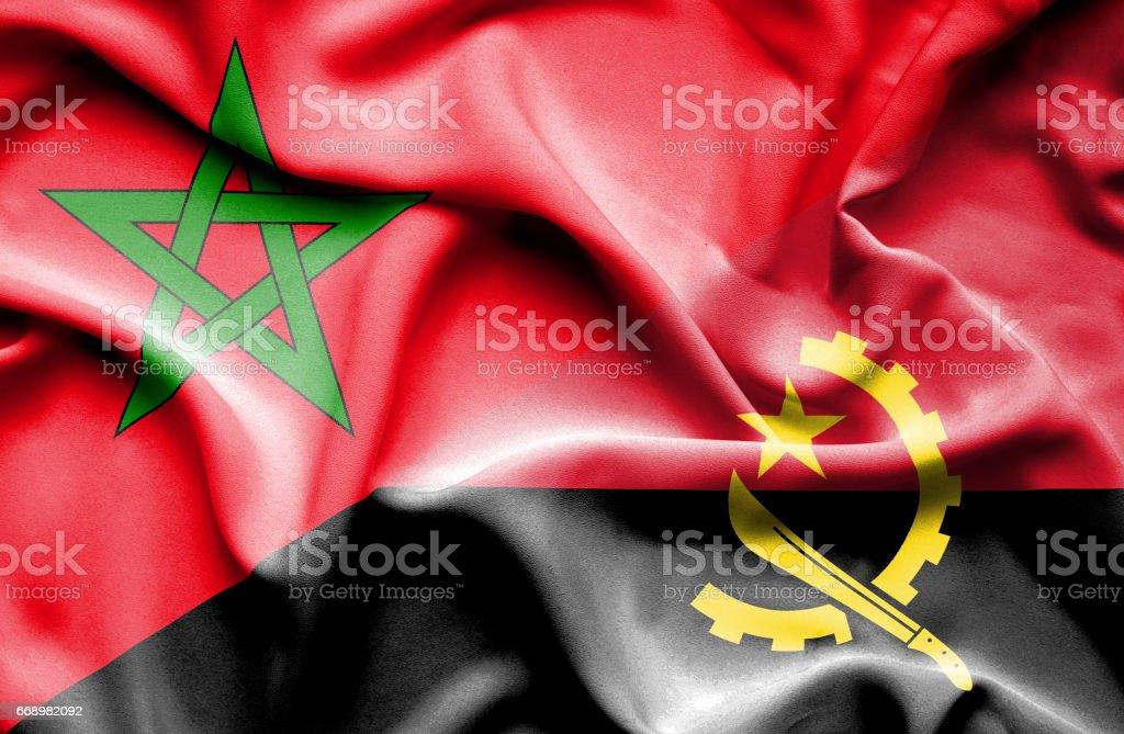 Waving flag of Angola and Morocco stock photo