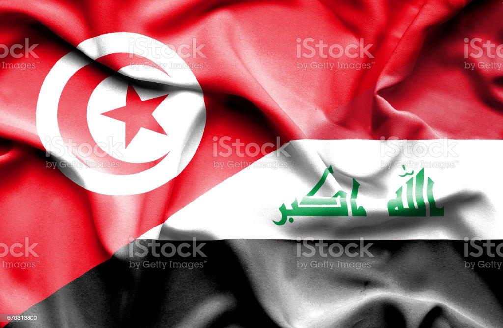Waving flag of Iraq and Tunisia stock photo