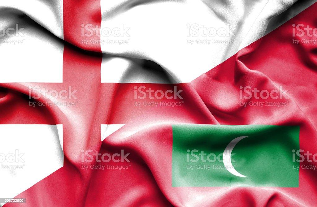 Waving flag of Maldives and England stock photo