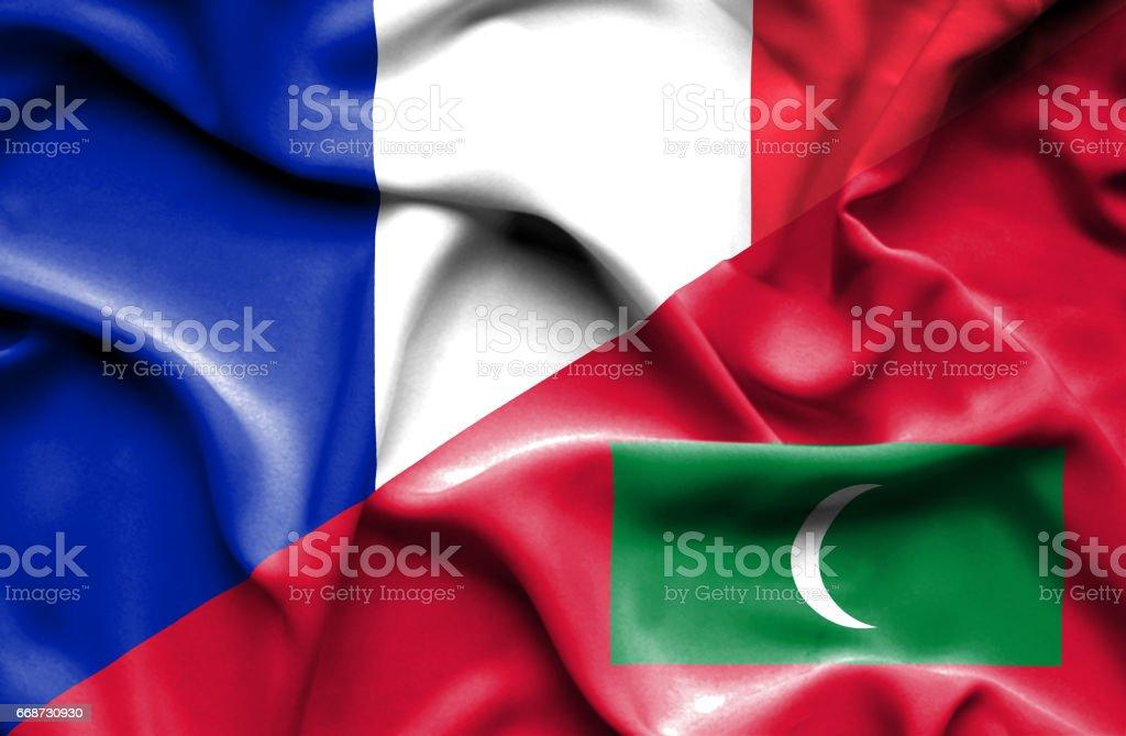 Waving flag of Maldives and France stock photo
