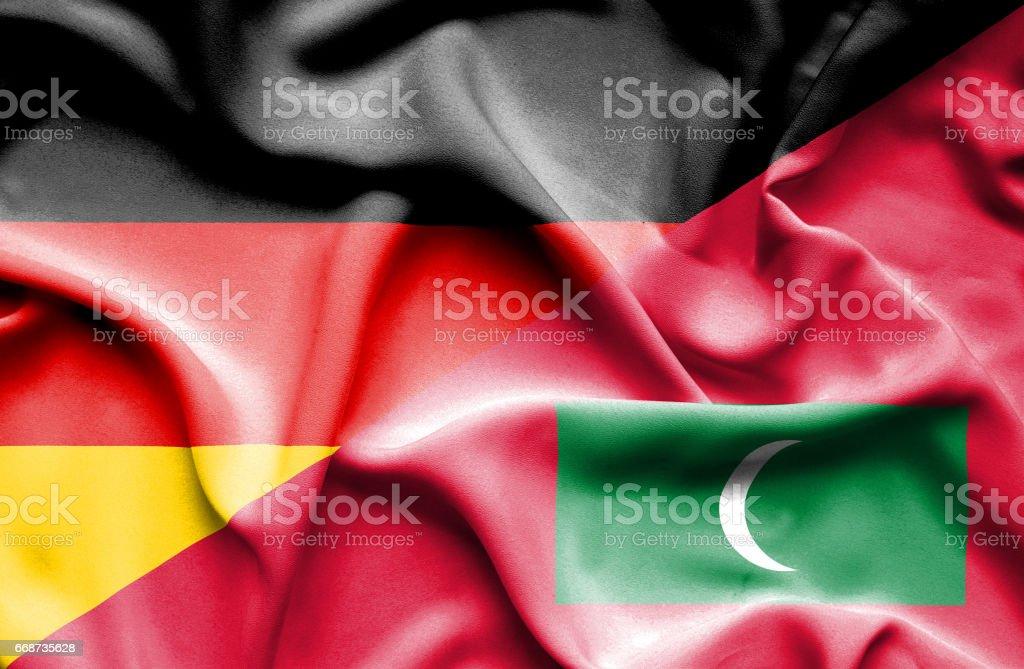 Waving flag of Maldives and Germany stock photo