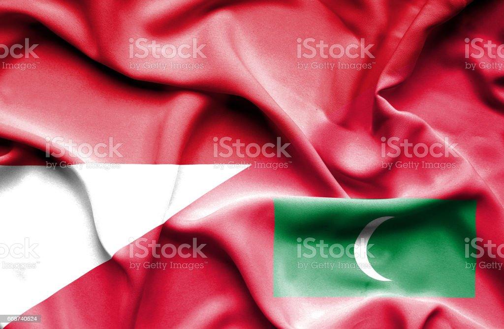 Waving flag of Maldives and Indonesia stock photo