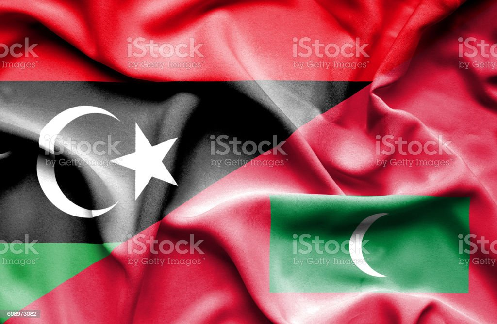 Waving flag of Maldives and Libya stock photo