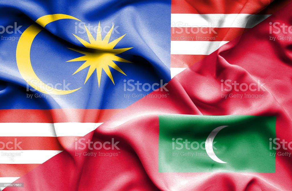 Waving flag of Maldives and Malaysia stock photo