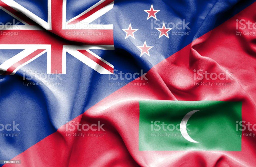 Waving flag of Maldives and New Zealand stock photo