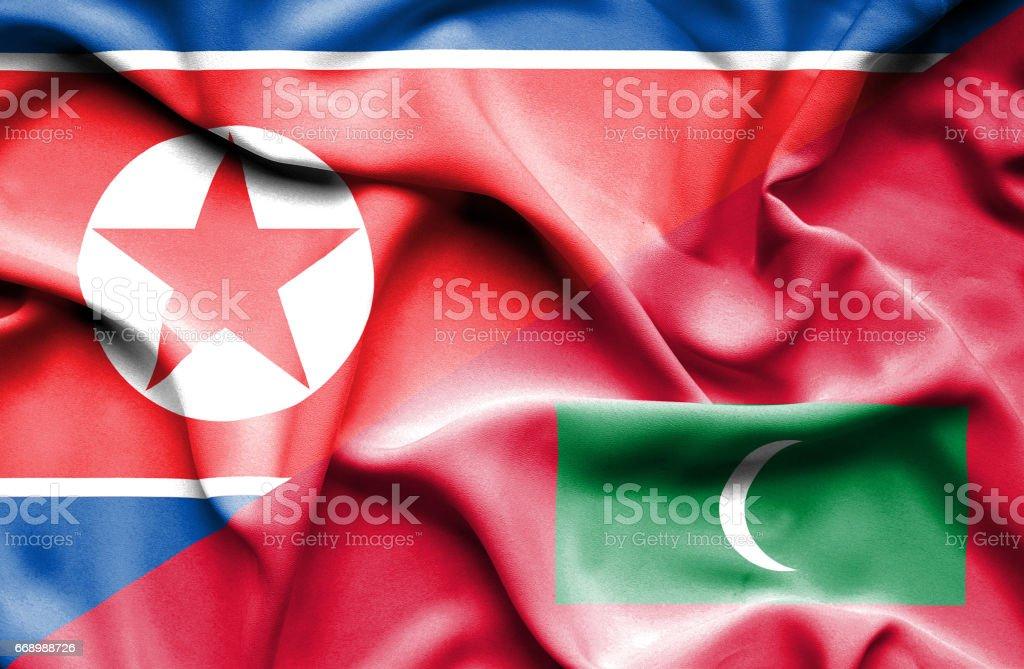 Waving flag of Maldives and North Korea stock photo