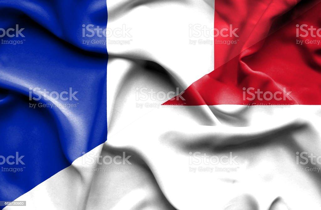 Waving flag of Monaco and France stock photo