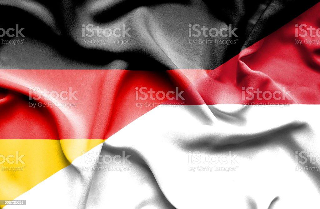 Waving flag of Monaco and Germany stock photo