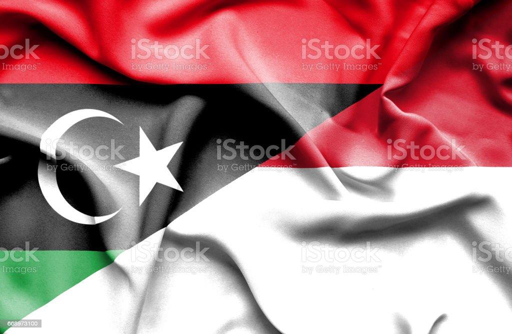 Waving flag of Monaco and Libya stock photo