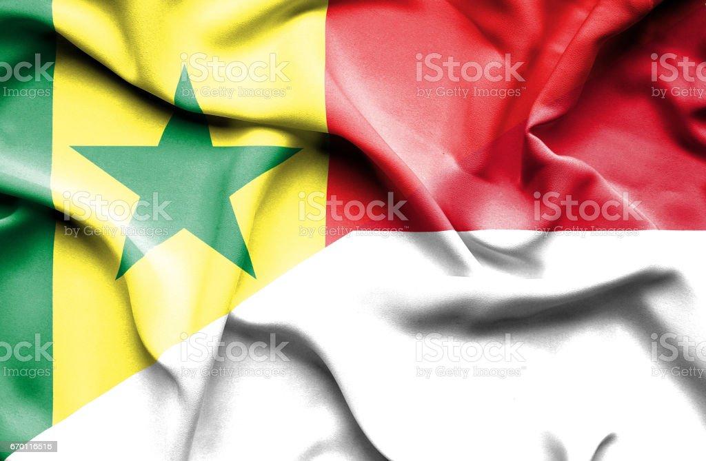 Waving flag of Monaco and Senegal stock photo