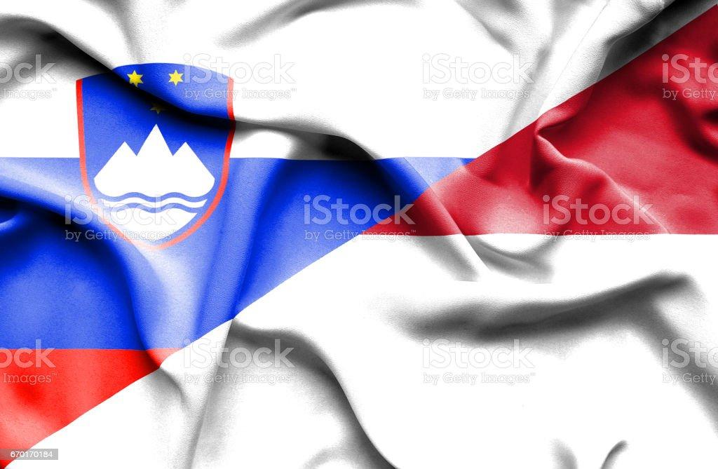 Waving flag of Monaco and Slovenia stock photo