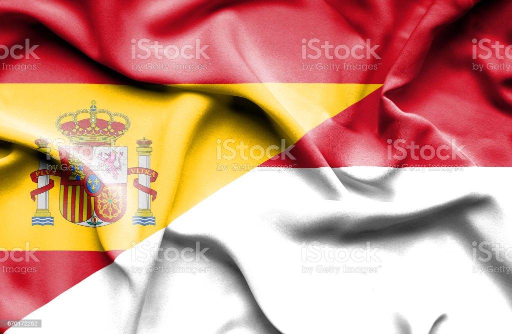 Waving flag of Monaco and Spain stock photo