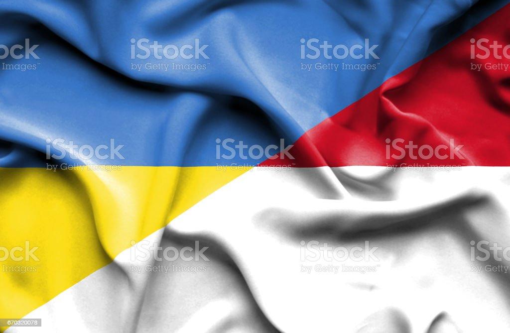 Waving flag of Monaco and Ukraine stock photo
