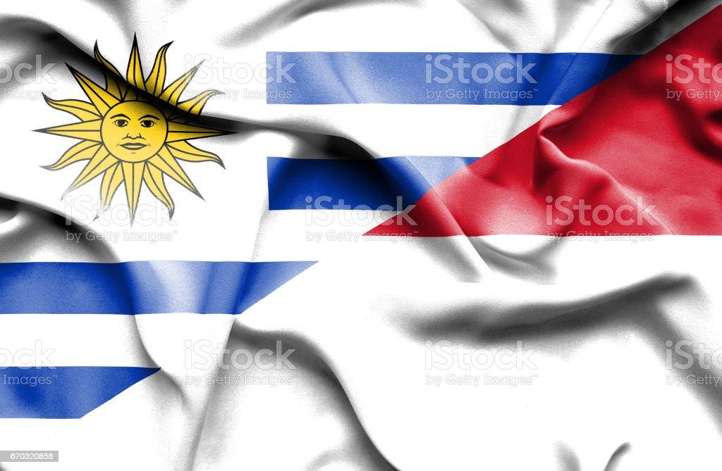 Waving flag of Monaco and Uruguay stock photo