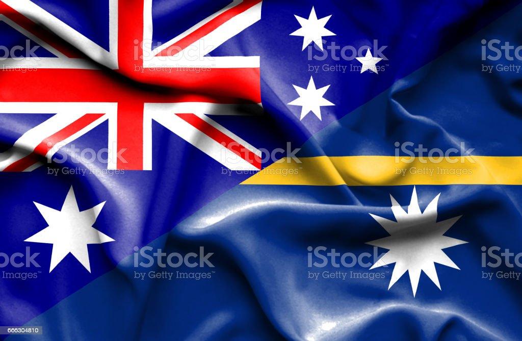 Waving flag of Nauru and Australia stock photo