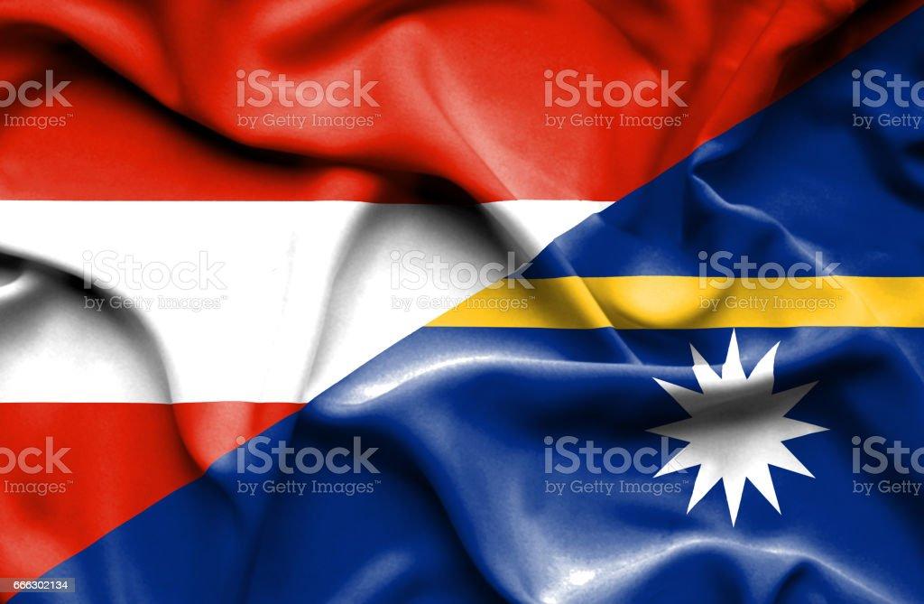 Waving flag of Nauru and Austria stock photo