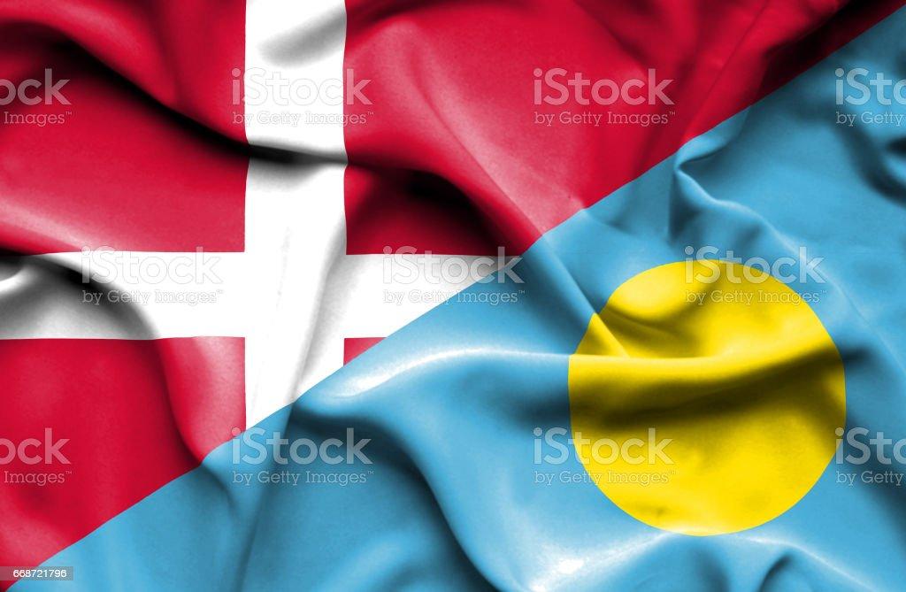 Waving flag of Palau and Denmark stock photo