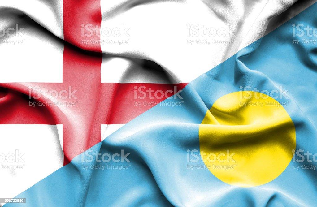 Waving flag of Palau and England stock photo