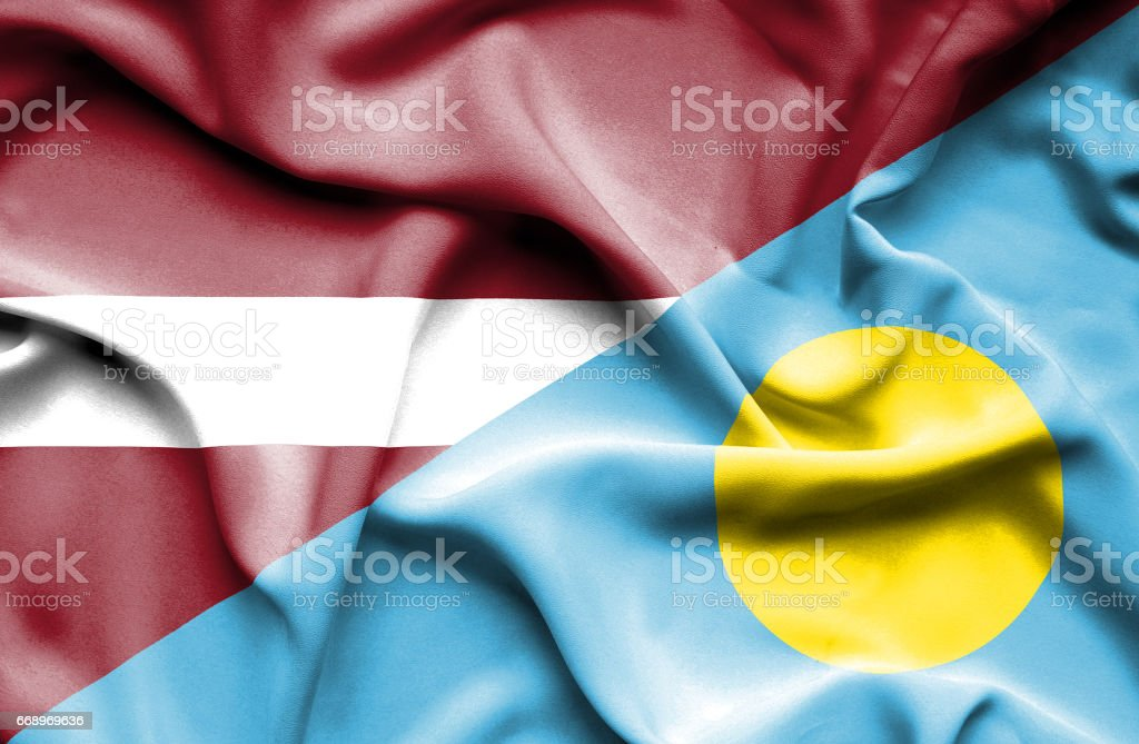 Waving flag of Palau and Latvia stock photo