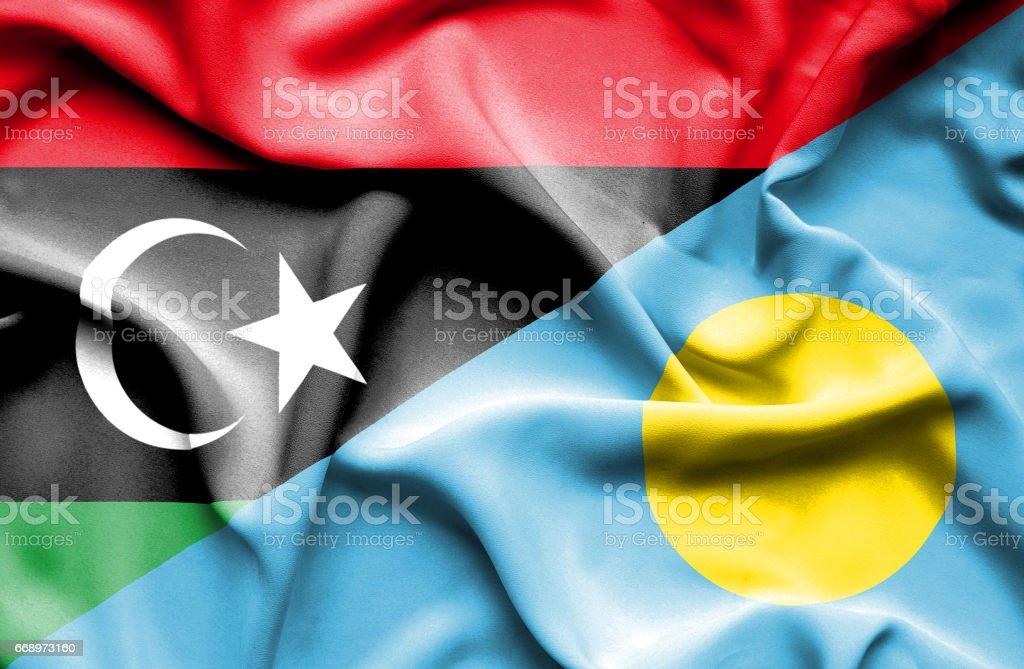 Waving flag of Palau and Libya stock photo