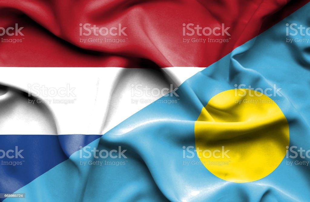 Waving flag of Palau and Netherlands stock photo